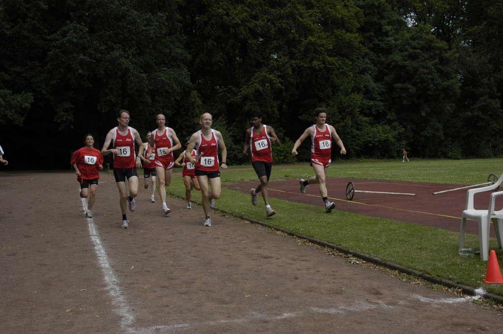 Die Staffelkollegen begleiten den letzten Läufer beim Zieleinlauf.